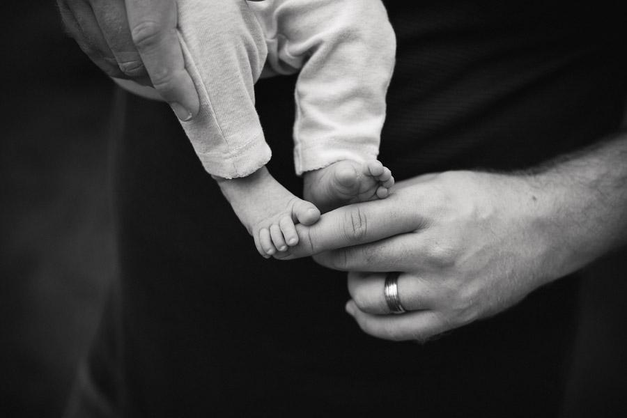 baby feet and daddy's hands - Newborn Photography Wayzata