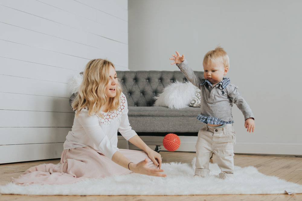 mommy and one year old boy playing with a red ball on a white rug - one year old baby photos