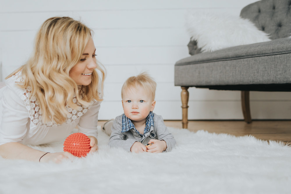 mommy and boy lying on a white rug - AMG Photography