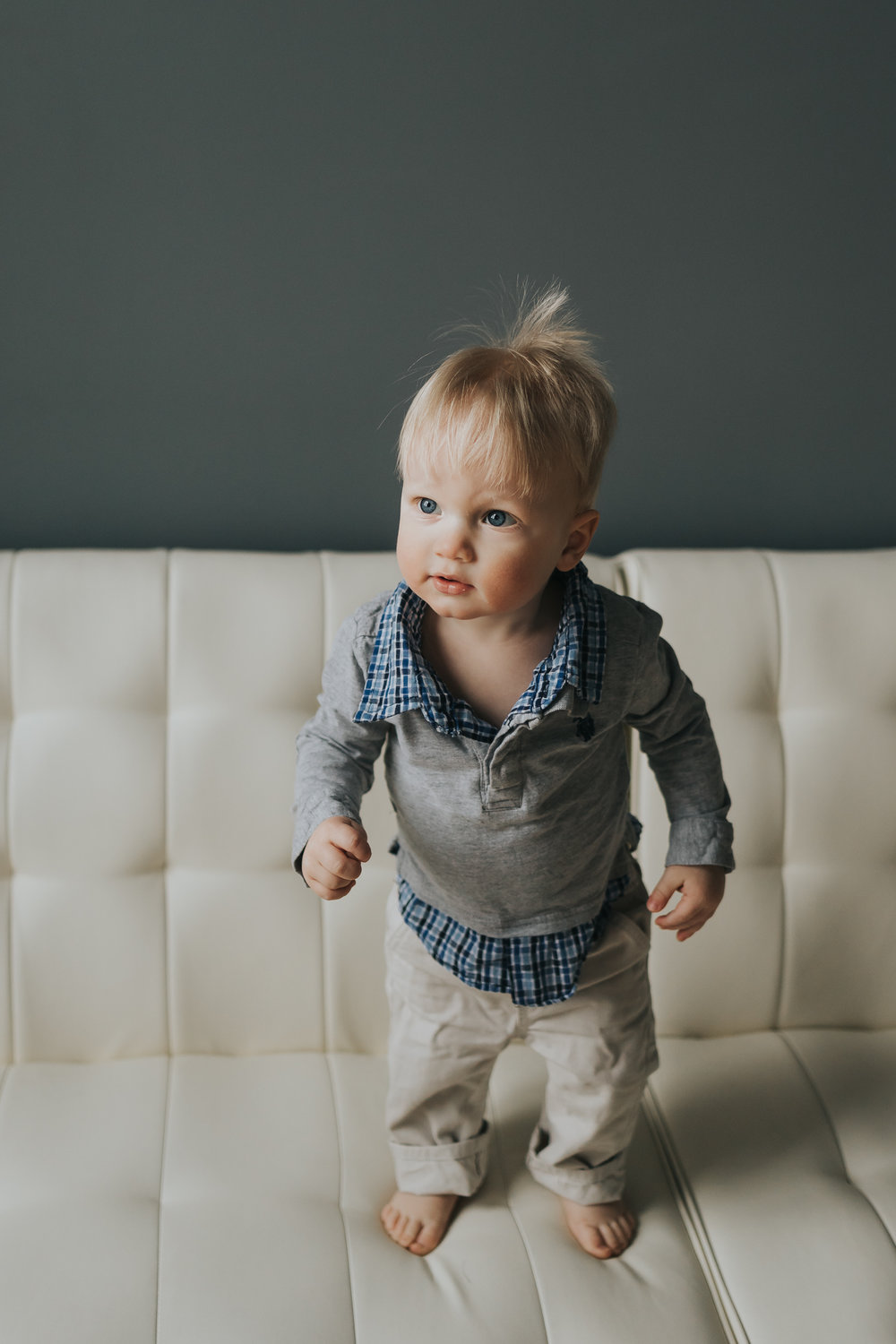one year old boy in gray sweater standing on white chair - AMG Photography