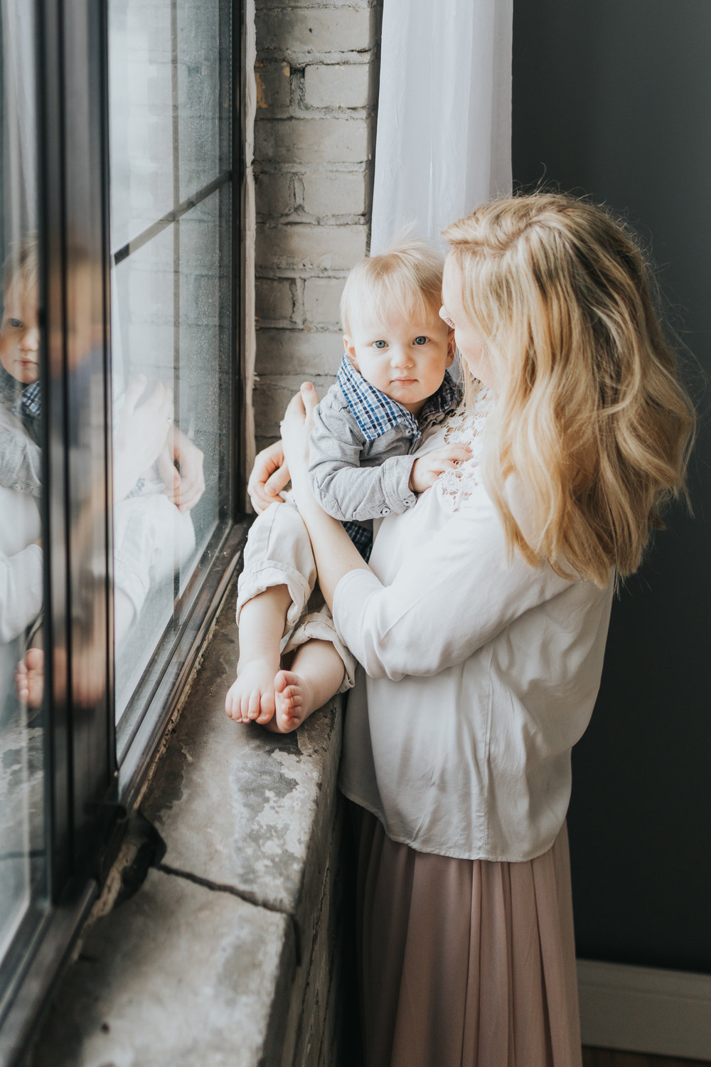 mommy holding baby boy by window - Minneapolis studio Photographer