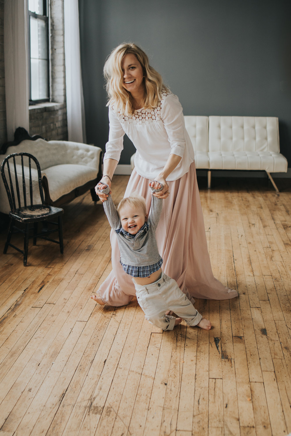 blonde woman in white shirt and pink skirt dancing with baby boy - Twin Cities Family Photographer