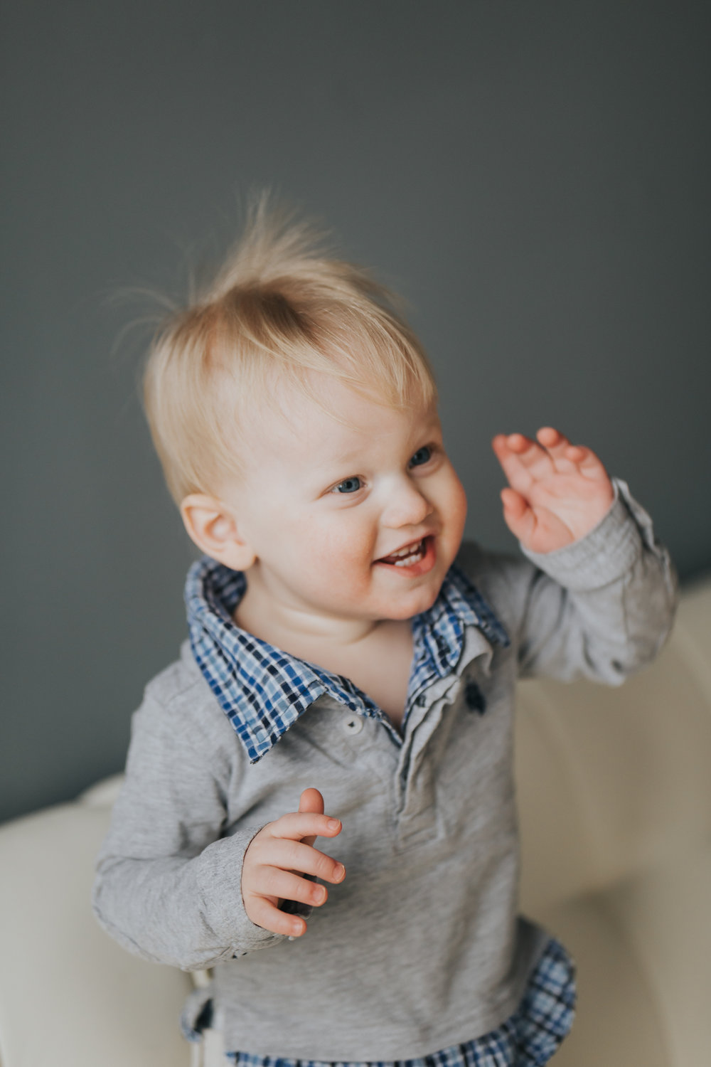 little boy with blonde hair waving and standing on white couch - Minnesota Baby Photographer