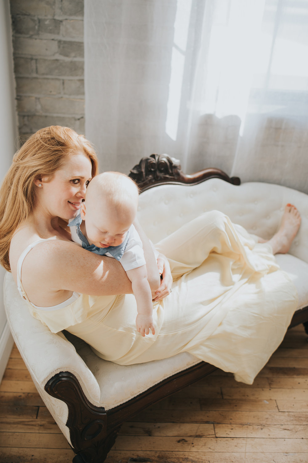 one year old baby boy cuddling with mother on white couch - Minnetonka Family Photographer