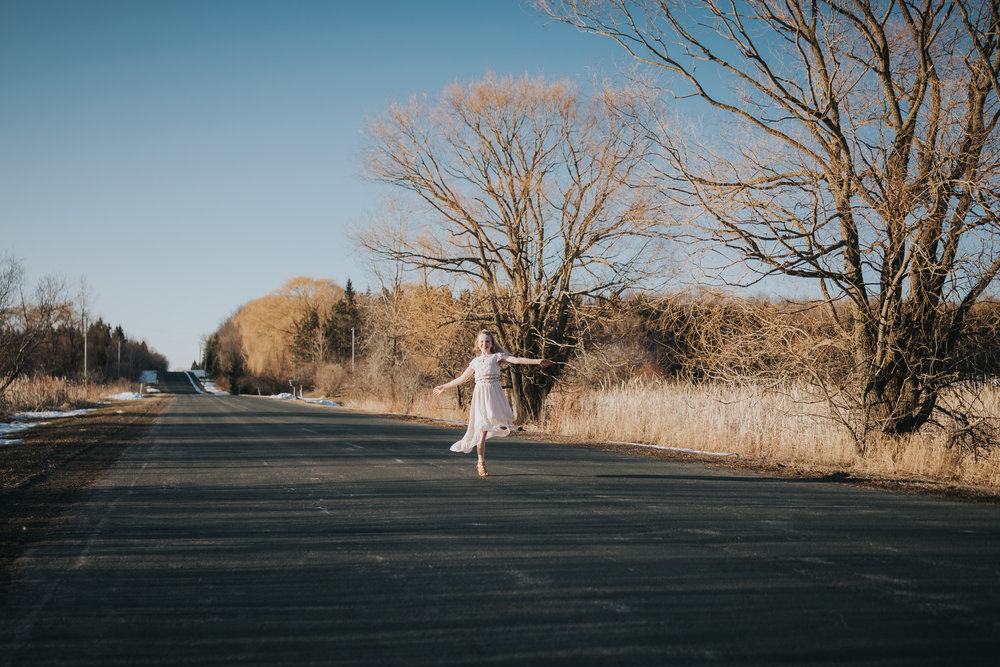 girl in pink dress dancing on a country road - Wayzata Family Photographer