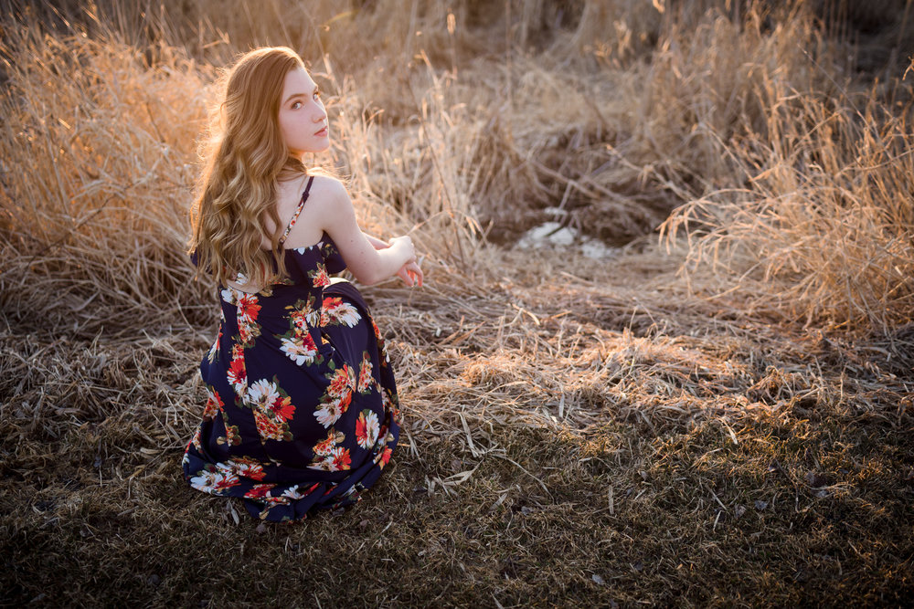 teenager sitting in a field in a flowered dress - Minneapolis Senior Photography
