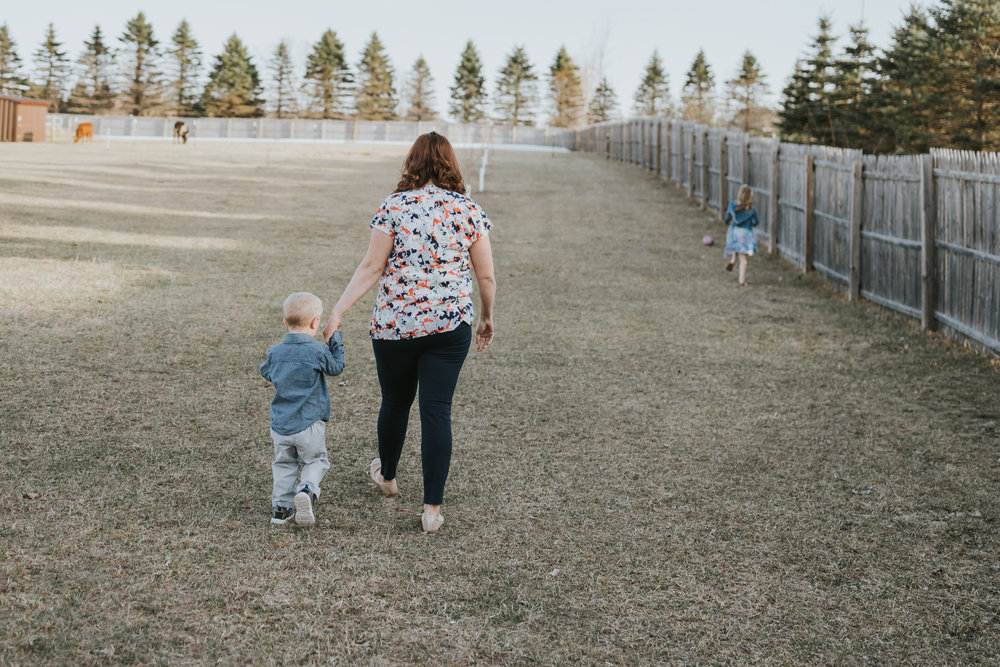 little boy walking with mommy in a field - Minnesota Special Needs Photographer