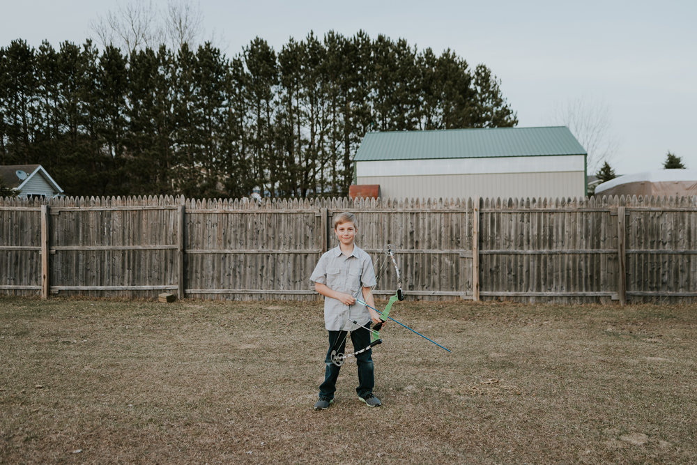 little boy standing with bow and arrow - Twin Cities Child Photographer