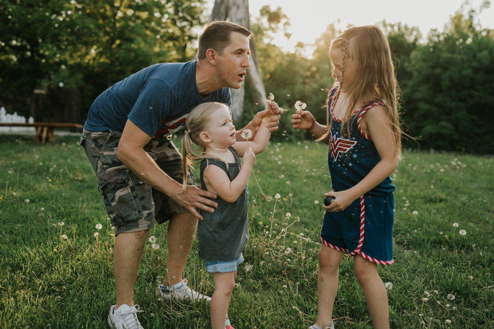 Daddy and two daughters blowing dandelions in the sun light - Minnetonka Family Photographer