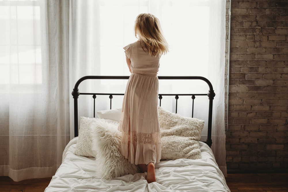 Teenage girl standing on a bed looking out the window - AMG Photography