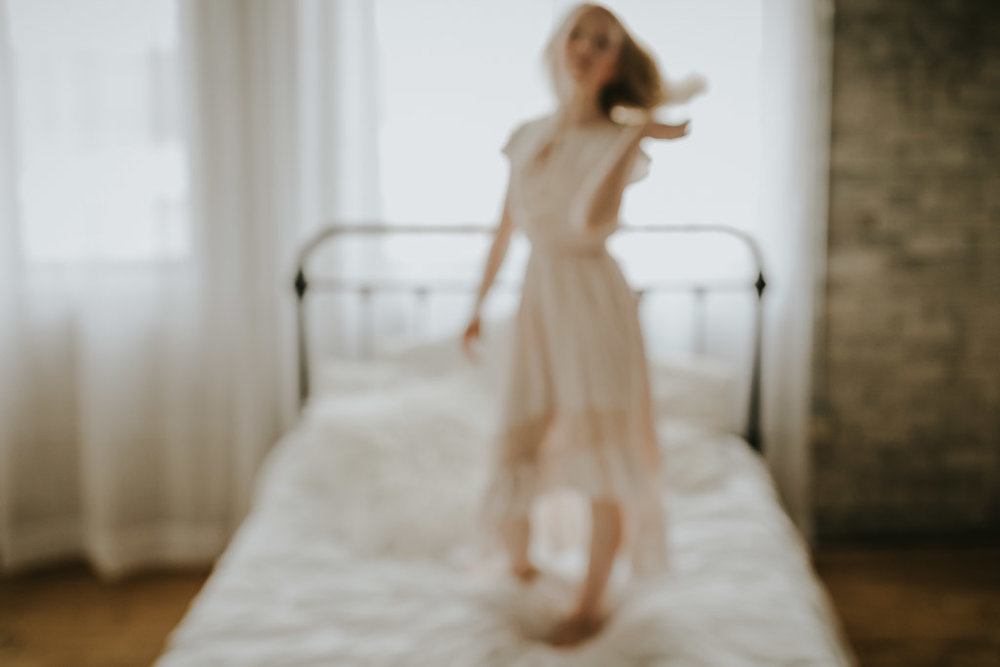 blurry image of girl on white bed - Minnesota Family Photgrapher