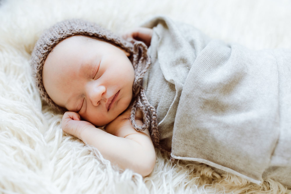 infant with brown bonnet and blanket - AMG Photography