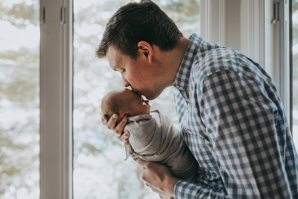 daddy kissing the head of his newborn boy - Minnesota Baby Photographer