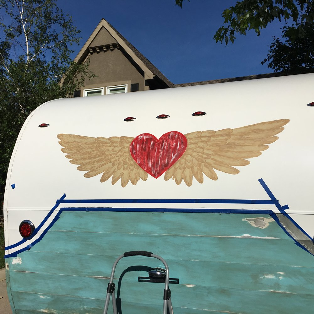 I drew out an outline of a sign that CAndice had found online and hand painted it on the back of the camper.