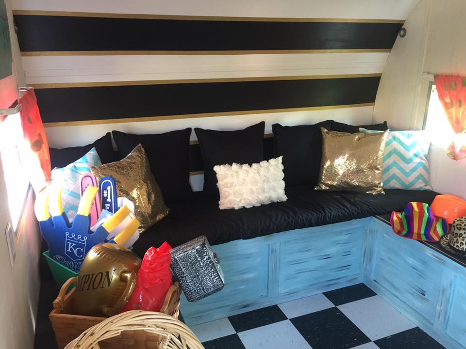The finished look with props ready to play! The backdrop has gold glitter, black & white stripes and we created a black cushion with fun pillows for comfortable seating. The benches were painted with a complementary blue and distressed with black, white and gold. Coral curtains with gold polka dots adorn the windows.