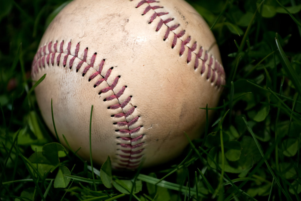 closeup-of-an-aged-and-worn-hardball-or-baseball-laying-in-the-green-grass-shallow-depth-of-field_rY5xrTD0Ss.jpg