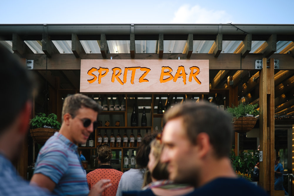 SPRITZ BAR    Nestled between the lower terrace and the upper terrace, the Spritz bar is the perfect place to unwind. Using produce from Pocket City Farms & local spirit, beer and wine suppliers, our Spritz bar offers a range of colorful & interesting drinks. The Spritz bar is covered in lush, hanging herbs & flowers which are used in our spritzes. The  'foraging bartenders'  pick the produce straight from the planters, while making the spritzes, and use them as garnish. The  bar menu  is Mediterranean inspired, with an outdoor wood fire oven to bring earth flavors to our mains.   Please note that we are fully licensed and not BYO.