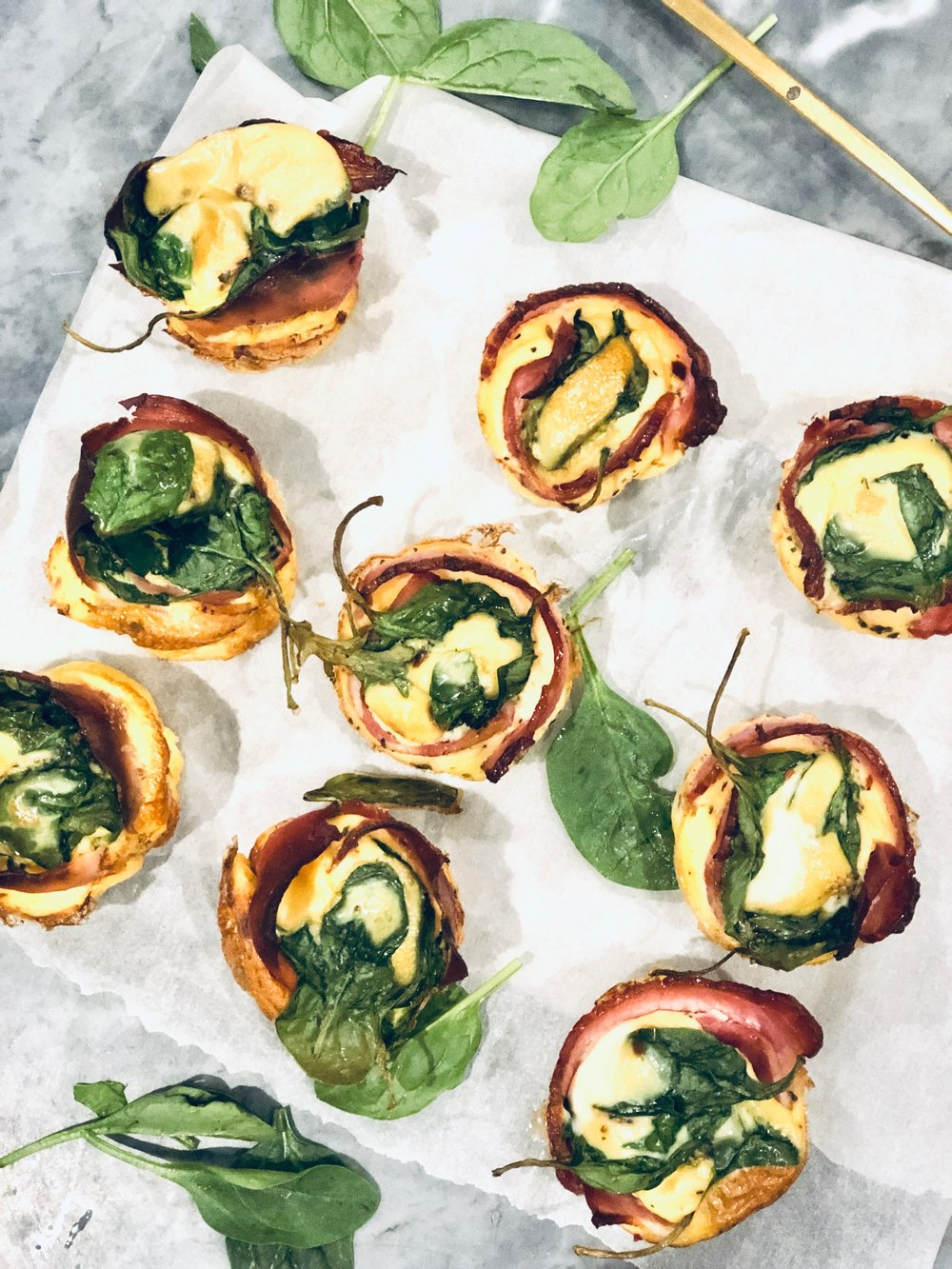 - Makes: 1 x dozen (Trust me you will want that many!)Ingredients12 eggsOptional: 12 slices very good quality smoked ham or bacon. If using bacon remove rind.1 teaspoon sea salt4 tbs flat leaf parsley (or whatever herbs you have on hand)Generous dash of cumin1 cup milk of choice (I use almond)Generous cup or two of spinachSun dried tomatoes (optional)100g Feta if you can tolerate dairy (more or less as desired)* Buy organic where possibleMethod1. Preheat oven to 180 degrees and either grease with coconut oil/butter or line muffin pan with squares of baking paper.2. Line each muffin mould with a rasher of the ham or bacon3. In large bowl, lightly whisk eggs, parsley, cumin, salt and milk.4. Add spinach, sprinkle through feta in chunks and sun dried tomatoes (if using)5. Divide egg mix between 12 muffin moulds. 6. Bake for 25 minutes, until ham/bacon is crisp and egg is just set.7. Enjoy as a meal or snack and be happy – these are so delicious!