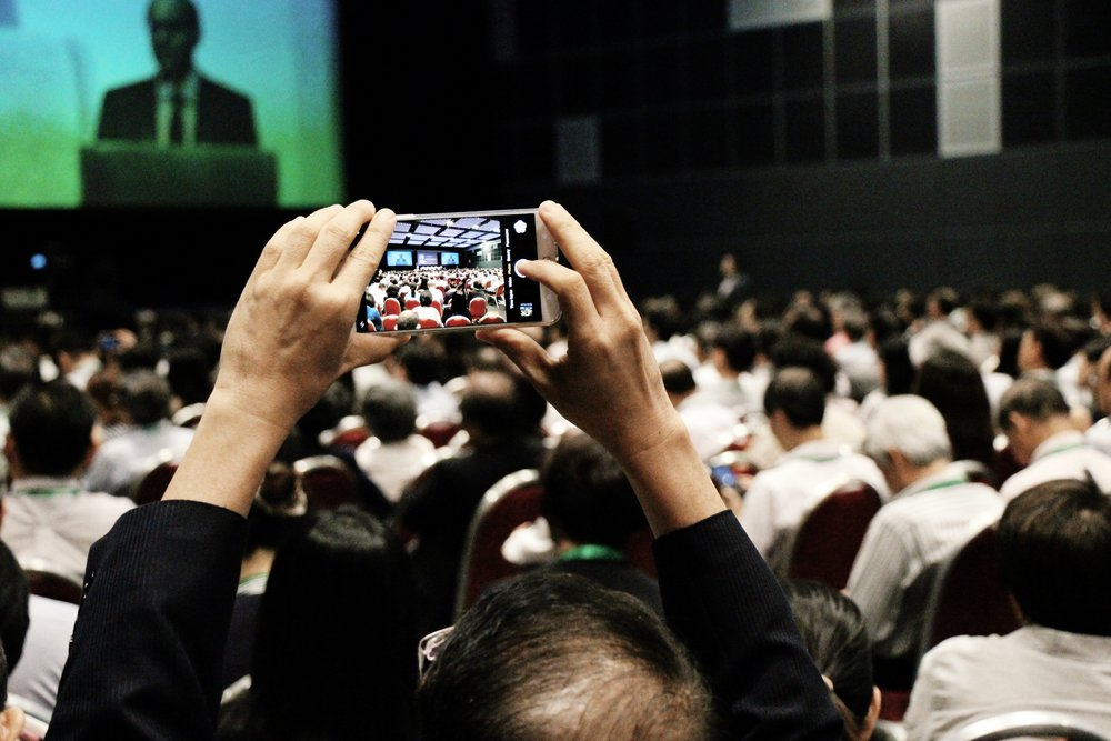 A delegate capturing a moment at the 19th Infocomm Conference 2016