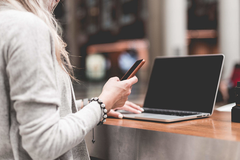 woman-using-her-smartphone-while-working-remotely-on-laptop_free_stock_photos_picjumbo_HNCK2998-2210x1474.jpg