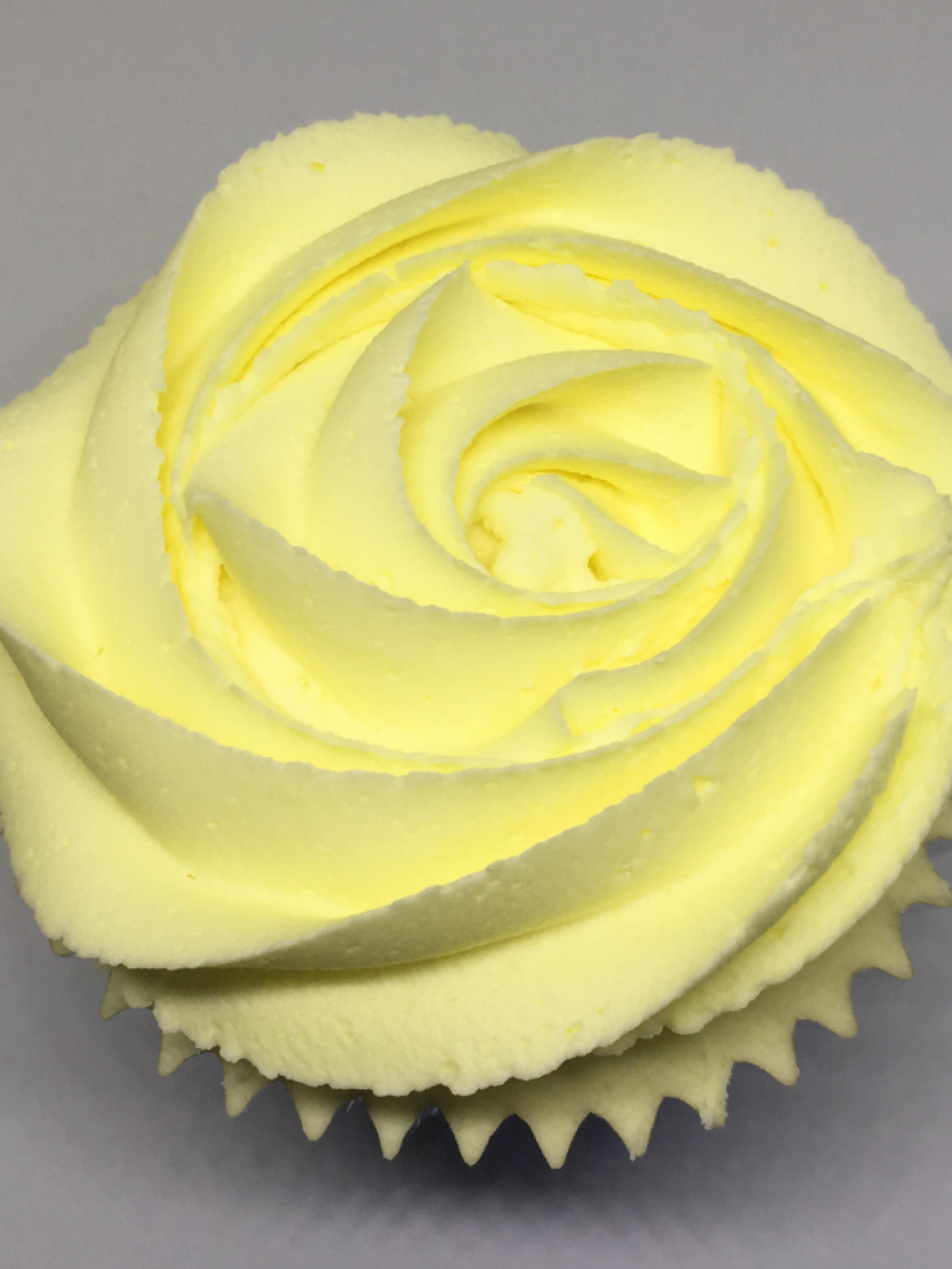 Lemon Drizzle - A luscious lemon cupcake with a tangy drizzle, filled with lemon curd and topped with zesty lemon buttercream