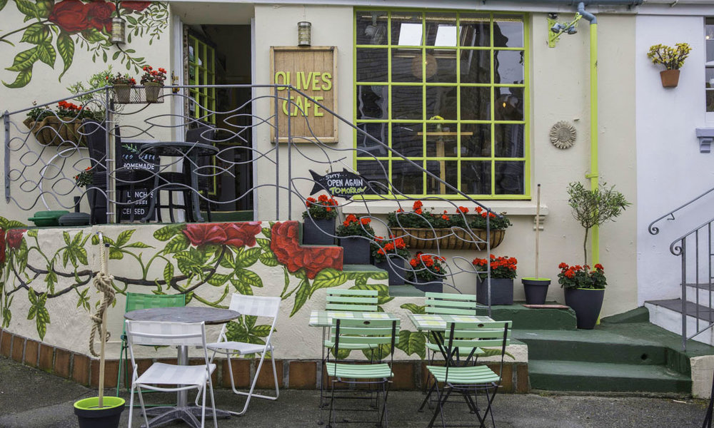 OLIVES CAFE - Sit indoors or outdoors and enjoy a selection of drinks including wine, Cornish beer or cider, soft drinks, coffees, teas; freshly made sandwiches, salads and homemade quiche. Indulge in one of their sumptuous cakes or a cream tea with freshly baked scones. Daily specials.07875 585759