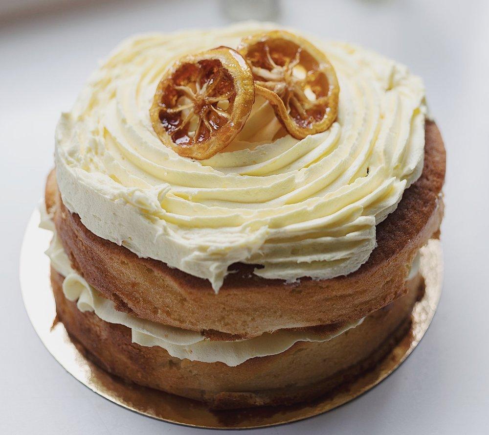 Lemon Curd Cake - Een super frisse citroen cake met citroentopping en plakjes citroen, de cake is goed voor ongeveer 16 personen. De prijs van deze taart is 33,50.