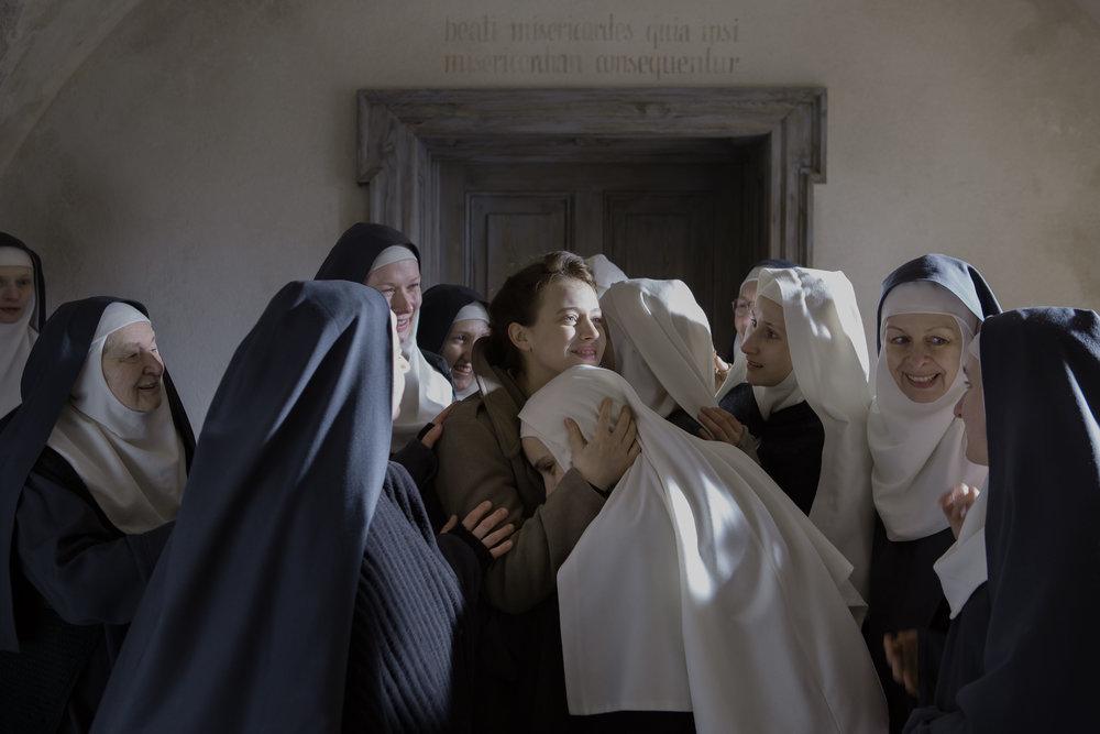 Et sterkt samhold vokser fram mellom kvinner fra ulike ståsted. I midten sees den ikke-troende legen Mathilde, omgitt av benediktinerklosterets nonner.