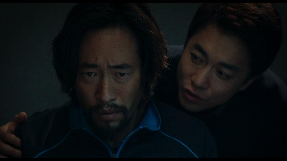 Den utspekulerte forhørslederen (Young-Min Kim) vil ha fiskeren Nam (Ryoo Seung-bum) til å tilstå at han er spion.