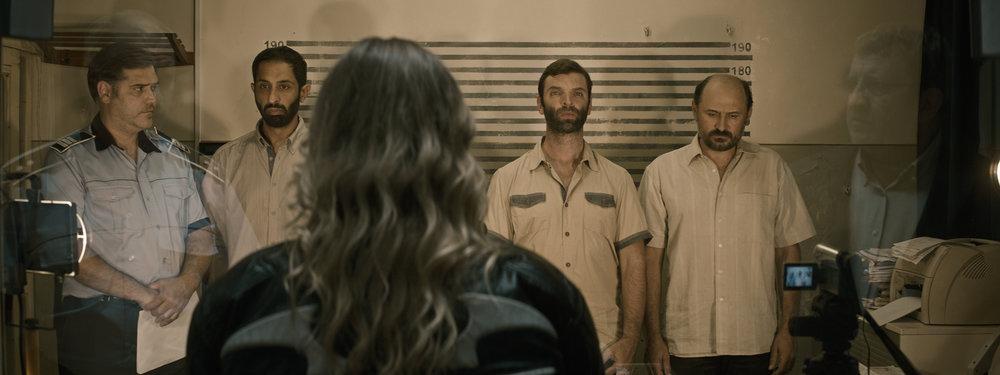 Datteren Eliza skal prøve å utpeke en overgrepsmann på politistasjonen. Farens ansikt speiler seg til høyre.