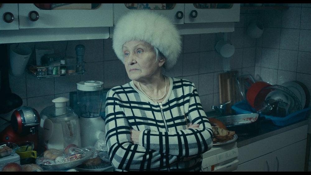 Lary, Relu og Sandras bestemor, Evelina (Tatiana Iekel) er en hissig forsvarer av kommunismen i Romania.