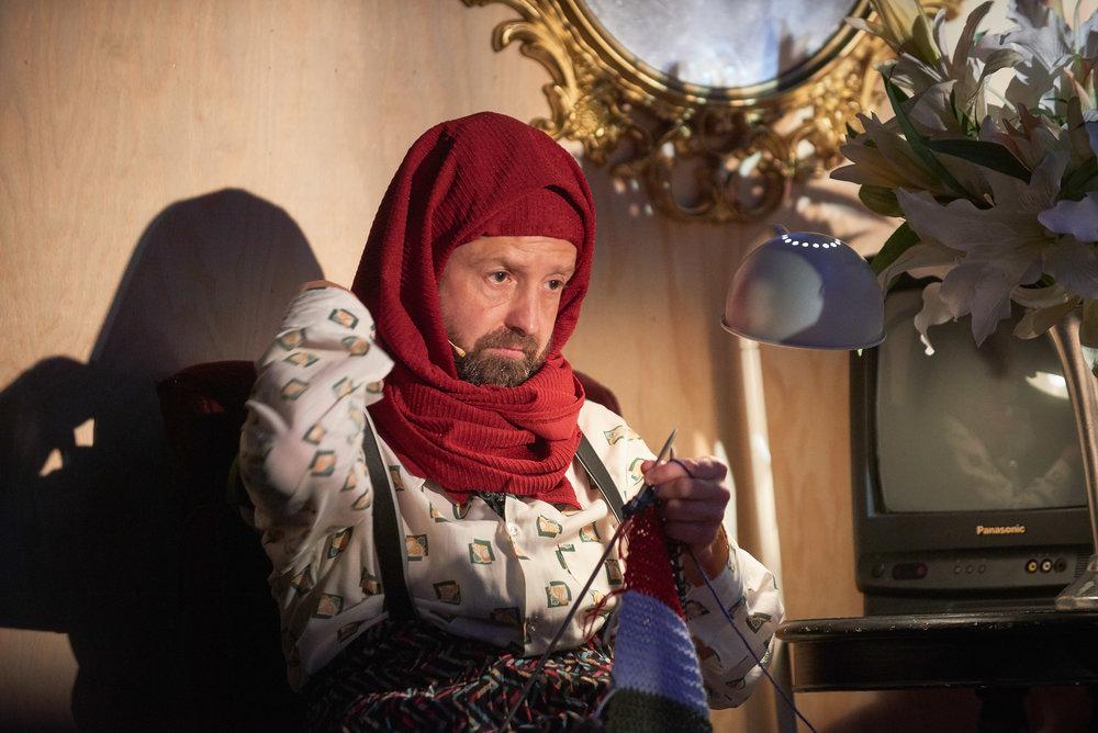 Asylsøkeren Randine er komisk iscenesatt av Lars Funderud Johannessen med skjegg og hijablignende sjal.