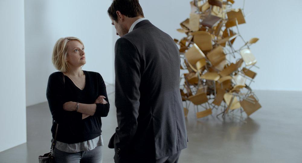 Går Christian stadig til sengs med kvinner fordi han har makt? Den pinlige samtalen mellom journalisten Anne (Elisabeth Moss) og museumssjef Juel Nilsen finner sted til bulderet fra stolskulpturen bak.