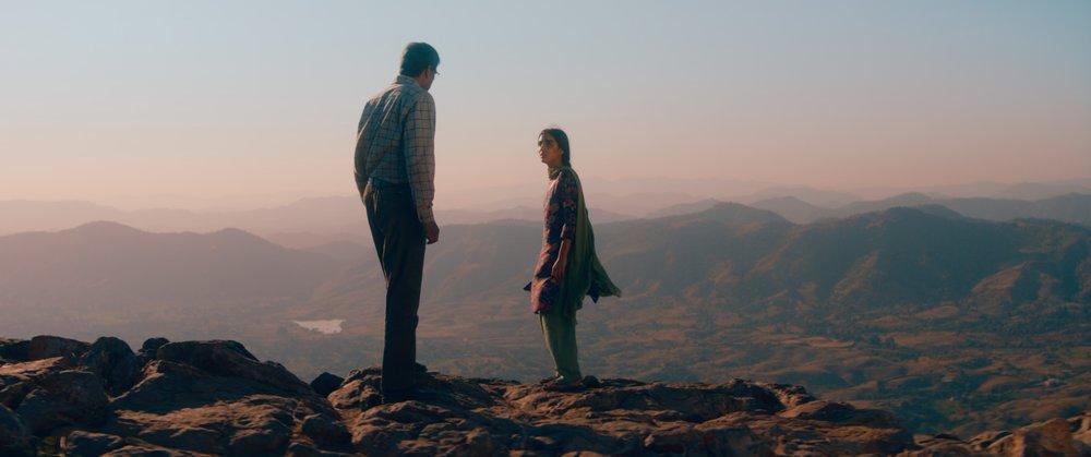 Dramatisk øyeblikk mellom far og datter med Pakistans fjell som bakgrunn.