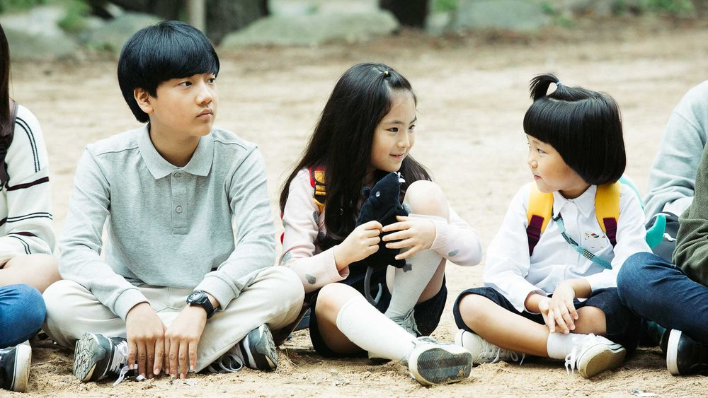 Familieforholdene er intrikate i  Home . 12 år gamle Jun-Ho (Lee Hyo-jae, til venstre) har felles mor med Sung-ho (i midten). Sistnevnte har felles far med halv-søsteren Ji-young.