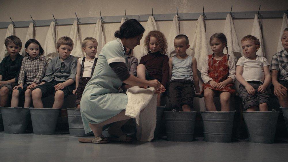 Barnehjembestyreren (Brynhildur Guðjónsdóttir) er skremmende streng i møte med barna som er sendt på sommerleir til en islandsk avkrok en gang på 1960-tallet.
