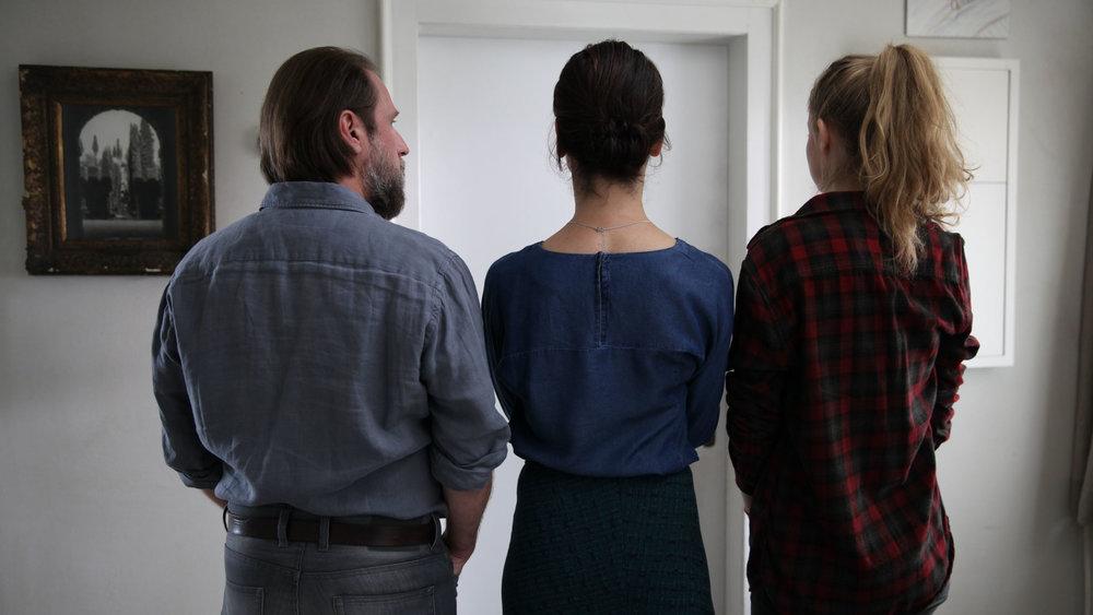 Far (Bjarne Mädel), mor (Bibiana Beglau) og datter (Emma Bading) står utenfor døra der familiens 17-åring har stengt seg inne for godt. Fra filmen  1000 Arten, den Regen zu beschreiben av Isabel Prahl.