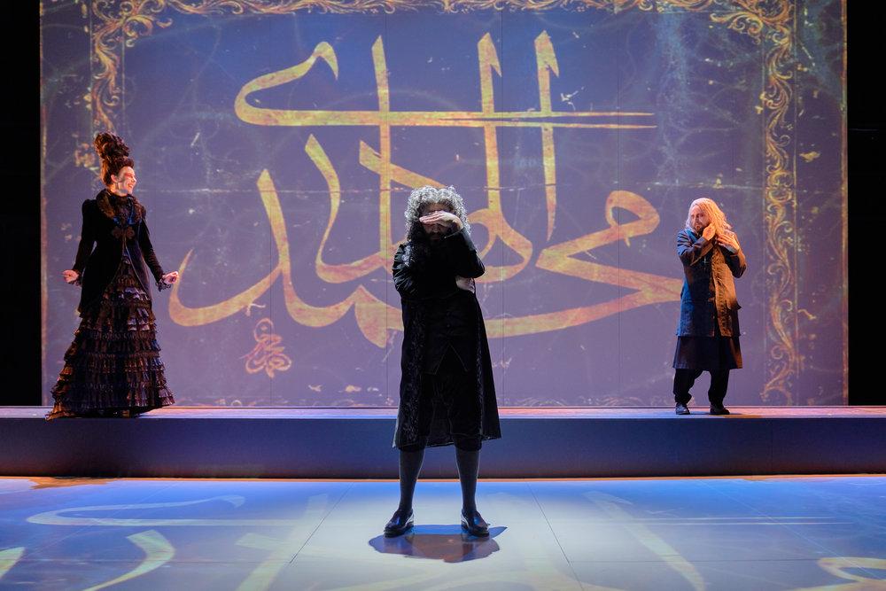 """Elmire (Ragnhild Tysse), Orgon (Even Stormoen) og Tartuffe (Anders Dale) foran videoprojeksjon av arabisk skrift som betyr """"Mohammed er føreren""""."""