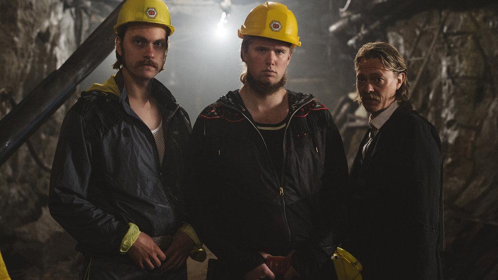 Gruveeieren (Ole Christoffer Ertvaag) flankert av medarbeideren (Arthur Berning) og den fremmede (Kristoffer Joner).