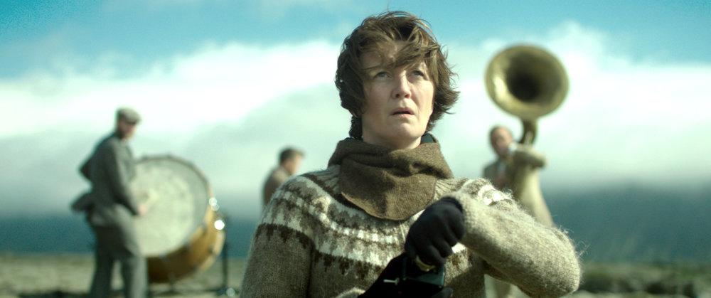 Ensomme Halla  omgis stadig av et orkester med tuba, trommer og trekkspill der hun kjemper ute i torven og langs landeveien.