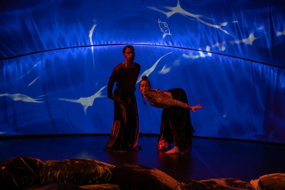 Over danserne med oppblåste kinn skimtes en av Per Dybvigs surrealistiske fisker. (Foto: dybwikdans/sandiland/flexer)