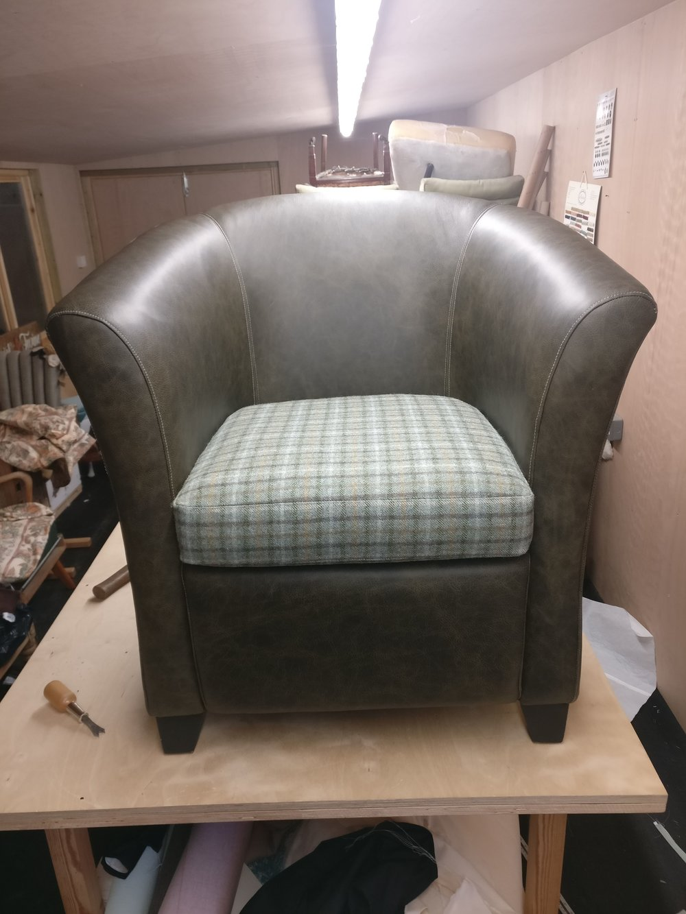 Grist & Twine Upholstery: Leather chair reupholstered in green with wool check cushion