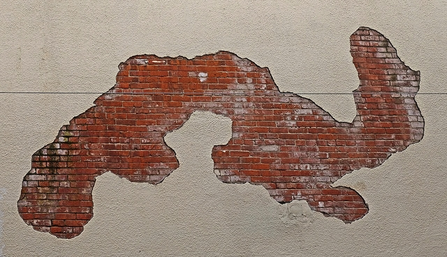 A wall with a hole shaped like a gerrymandered district. Source: Flickr