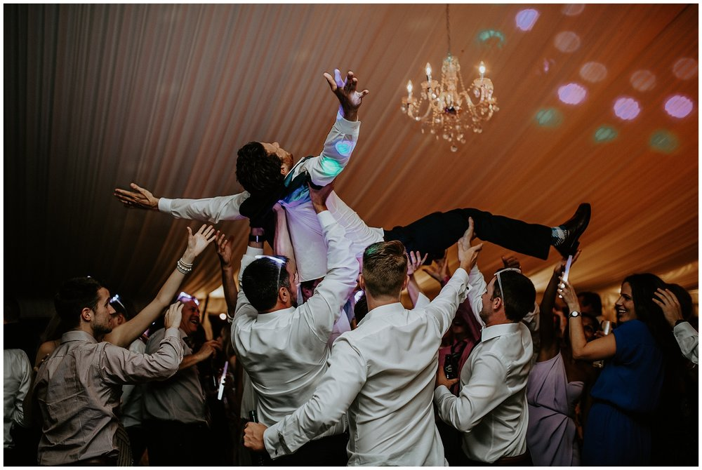 Crowd surfing groom on the dance floor at a Hart House wedding