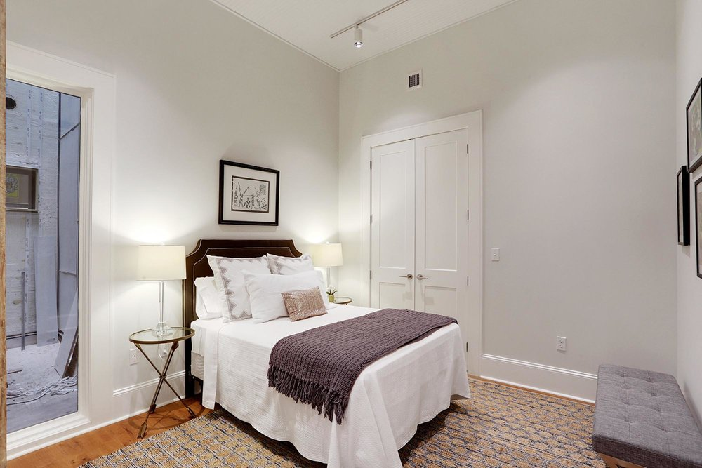 Bedroom with mirror and art hanging over bed