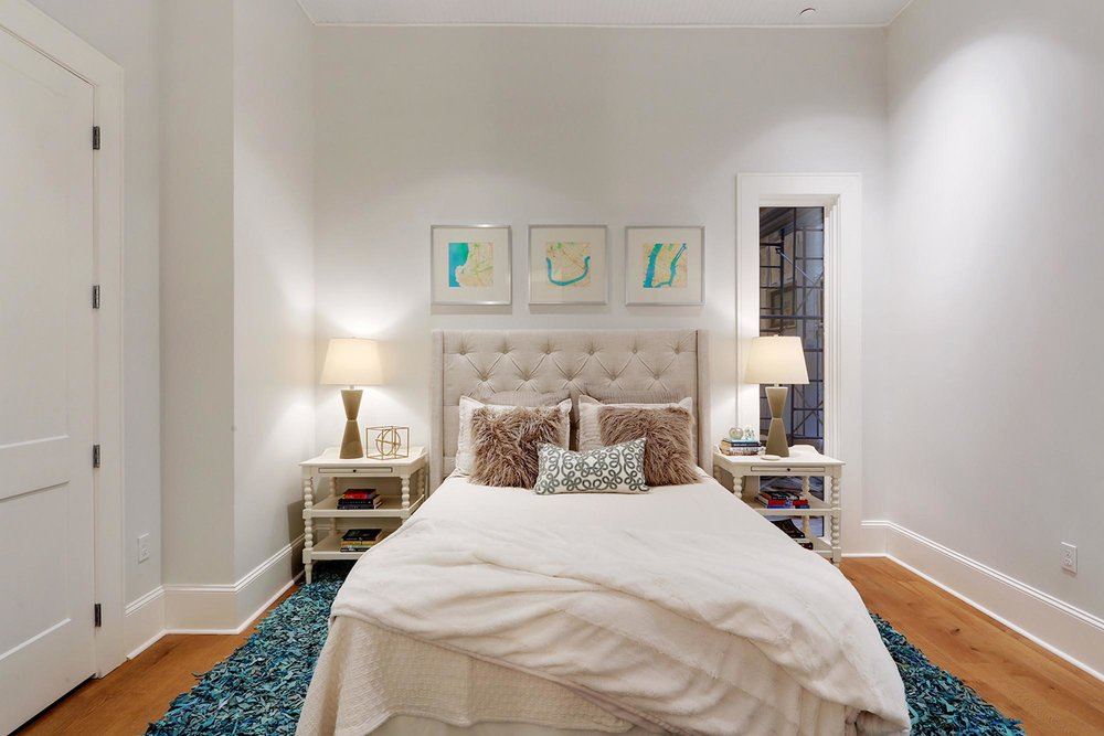Stylish bedroom with blue shag rug and white bedside tables
