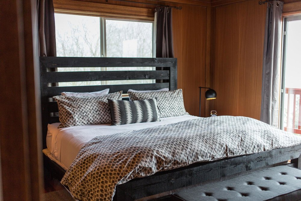 King bed with graphic bedding and wood paneling