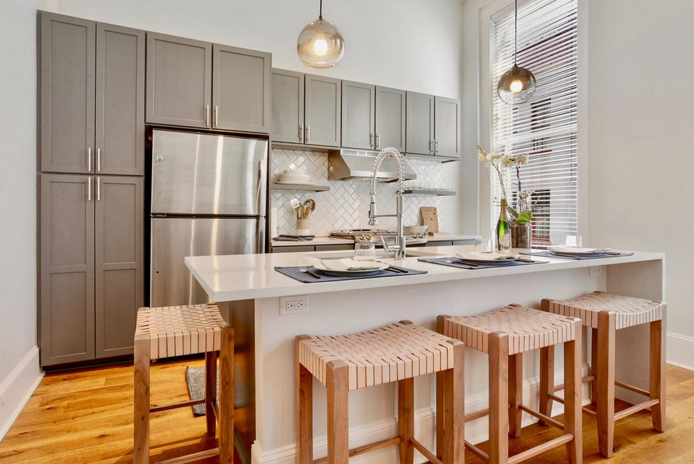 Modern kitchen area with white quartz island and wooden stools