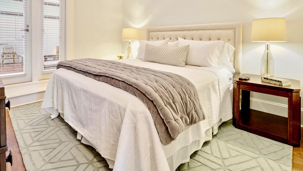 Bright white and navy bedroom with x bedside tables and lucite lamps