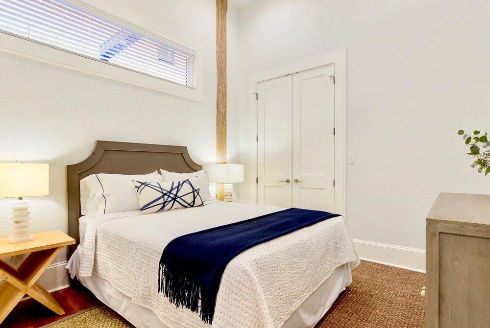 Bedroom with horizontal eyebrow window over bed